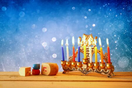 chanukah: low key image of jewish holiday Hanukkah with menorah traditional Candelabra and wooden dreidels spinning top. glitter background