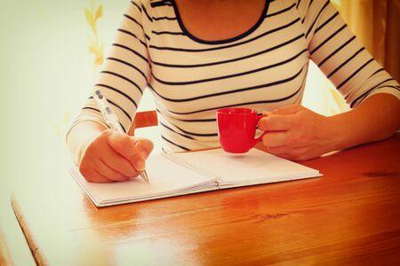 escritura: Mujer joven que se sienta cerca de la ventana y la escritura. filtrada retro imagen. fotografía con luz natural de la ventana. enfoque selectivo
