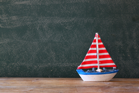 discover: photo of wooden sailing boat in front of chalkboard