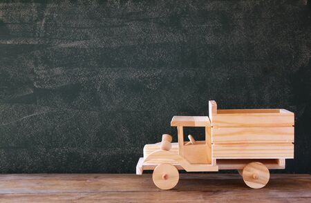 wooden toy: photo of wooden toy truck in front of chalkboard
