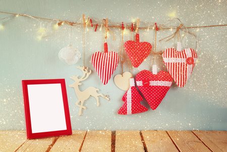 christmas red: christmas image of fabric red hearts and blank frame, garland lights, hanging on rope in front of blue wooden background. retro filtered. Template ready to put photography Stock Photo
