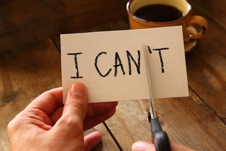 attitude: hombre tarjeta de explotación de la mano con el texto que no se puede, cortando la palabra t por lo que por escrito que puedo. el éxito y el concepto de desafío. imagen de estilo retro
