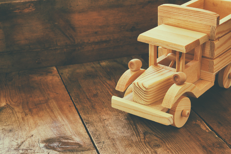 wooden toy: retro wooden toy car over wooden table. room for text. nostalgia and simplicity concept. retro style image Stock Photo