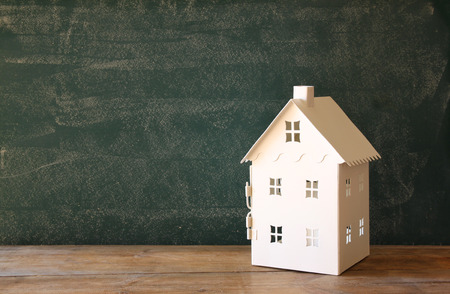 room for text: miniature toy house over chalkboard background. room for text Stock Photo