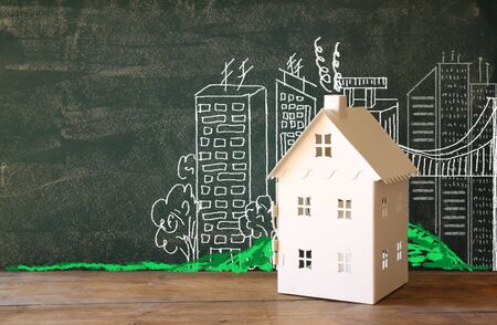 loans: photo of house and background of blackboard and city drawings. real estate and family house concept