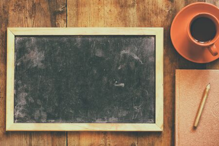 top view image of empty blackboard next to cup of coffee and notebook, over wooden table. image with retro style filter Stock Photo