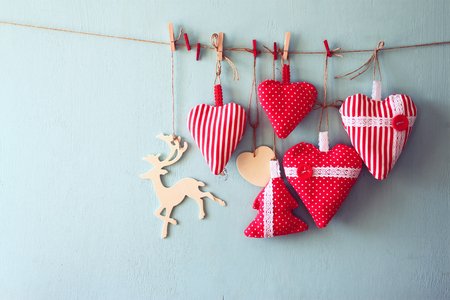 christmas red: christmas image of fabric red hearts and tree, wooden reindeer, hanging on rope in front of blue wooden background. retro filtered Stock Photo