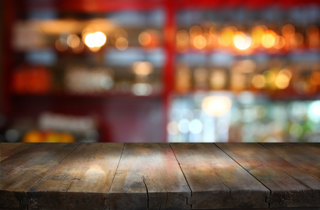 blurry: image of wooden table in front of abstract blurred background of restaurant lights