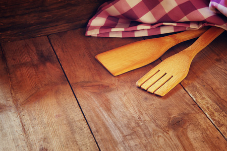 wooden kitchen utensils and table cloth on wooden table