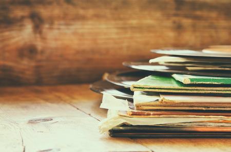 sixties: selective focus of records stack with record on top over wooden table. vintage filtered