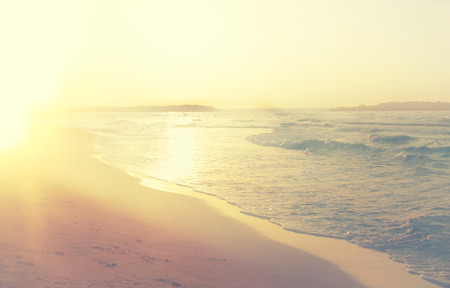 paradise beach: background of blurred beach and sea waves, vintage filter.