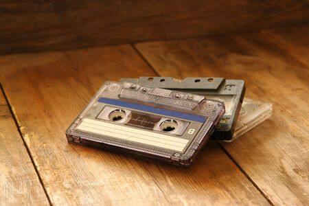 indie: selective focus of Cassette tape over wooden table. image is instagram style filtered. Stock Photo