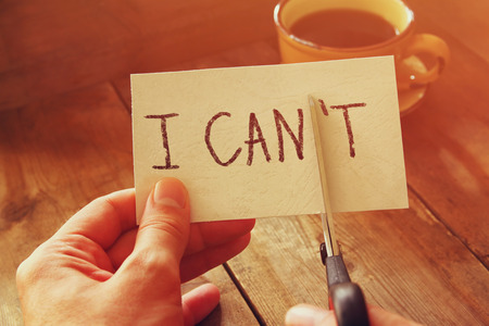 cant: man hand holding card with the text i cant, cutting the word t so it written i can. success and challenge concept. retro style image