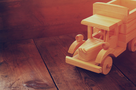 nostalgy: retro wooden toy car over wooden table. room for text. nostalgia and simplicity concept. retro style image Stock Photo