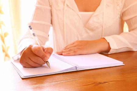 jeune femme assise près de la fenêtre et de l'écriture. Rétro image filtrée. photo avec fenêtre lumière naturelle. mise au point sélective