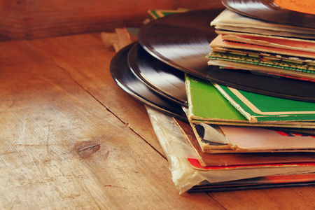 record label: selective focus of records stack with record on top over wooden table. vintage filtered
