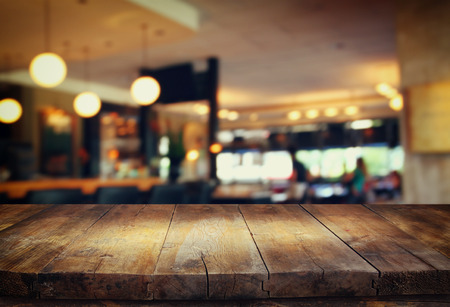 shop interior: image of wooden table in front of abstract blurred background of restaurant lights
