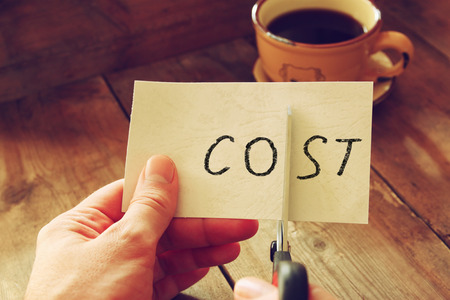 man hands cutting card with the word cost. business concept, cutting costs Stockfoto