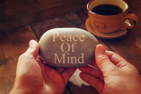 braveness: hands holding pebble stone with the phrase piece of mind