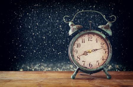polvo: imagen del reloj de alarma de la vendimia en la mesa de madera delante de la plata m�gica del brillo y las luces de fondo negro. filtrada retro