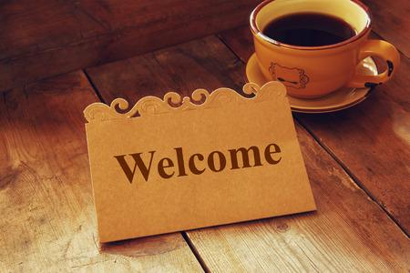 bienvenida: tarjeta de bienvenida sobre la mesa de madera junto a la taza de café Foto de archivo
