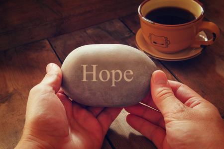 hands holding pebble stone with the word hope