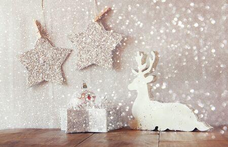 reno: Imagen de madera blancas estrellas de renos y brillo colgando de una cuerda sobre fondo de plata brillo. retro filtrada con la capa de brillo