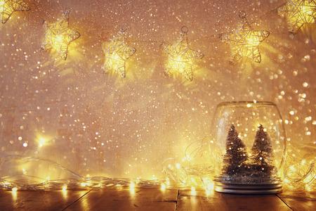 imagen: imagen de los árboles de navidad bajo llave y la vendimia se filtraron en frasco de vidrio con luces cálidas guirnalda. enfoque selectivo
