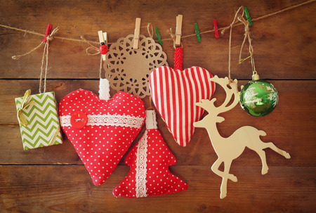 wooden reindeer: Christmas image of fabric red hearts and tree. wooden reindeer and garland lights, hanging on rope in front of wooden background Stock Photo