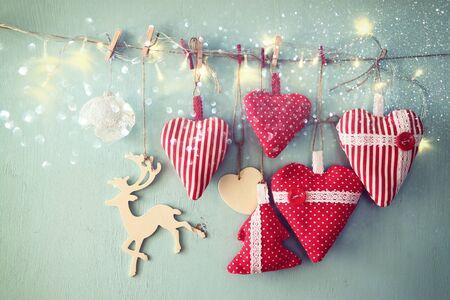 wooden reindeer: christmas image of fabric red hearts and tree. wooden reindeer and garland lights, hanging on rope in front of blue wooden background. retro filtered with glitter overlay