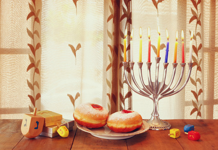 dreidels: image of jewish holiday Hanukkah with menorah traditional Candelabra and wooden dreidels spinning top on table in front of the window
