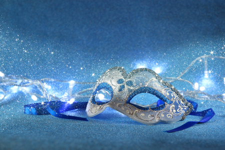 carnival party: blue female carnival mask and glitter background. with glitter overlay