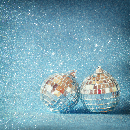 broshure: image of christmas festive decorations on blue glitter background. retro filtered with glitter overlay. selective focus Stock Photo