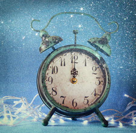 12 oclock: vintage clock over blue ice bokeh background. new year concept. selective focus
