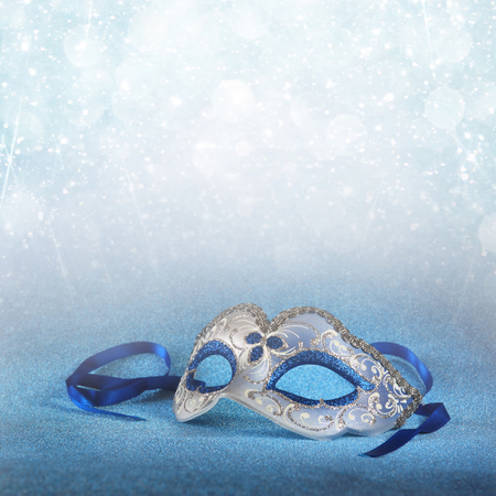 masquerade: blue female carnival mask and glitter background. with glitter overlay