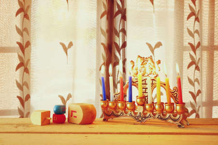 hanukkah: image of jewish holiday Hanukkah with menorah traditional Candelabra and wooden dreidels spinning top
