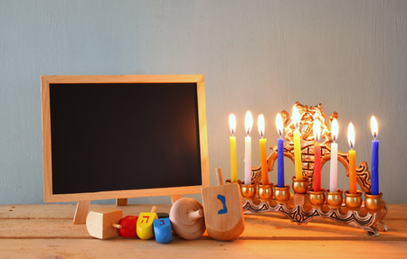 hanukka: image of jewish holiday Hanukkah with wooden colorful dreidels spinning top with chalkboard background Stock Photo