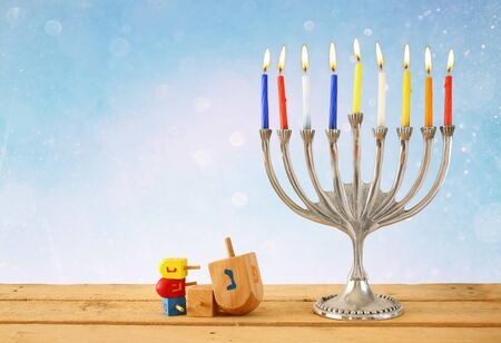 dreidels: image of jewish holiday Hanukkah with menorah traditional Candelabra and wooden dreidels spinning top