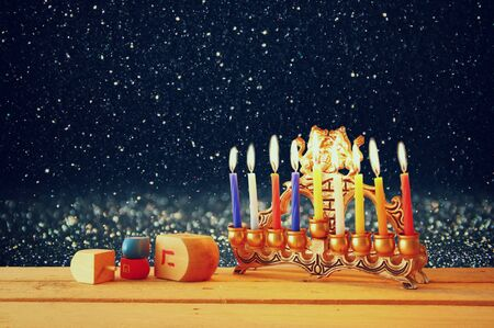 image of jewish holiday Hanukkah with menorah traditional Candelabra and wooden dreidels spinning top