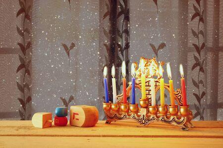 dreidels: image of jewish holiday Hanukkah with menorah traditional Candelabra and wooden dreidels spinning top