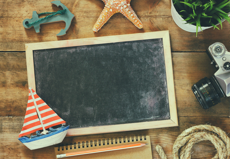 sailboat: top view image of blank old chalkboard, wooden sailboat, nautical ripe, notebook and camera. travel and adventure concept