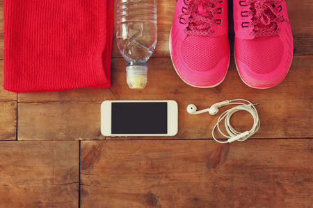motion: fitness koncept med mobiltelefon med hörlurar, handduk och kvinna sport skor över trä bakgrund.