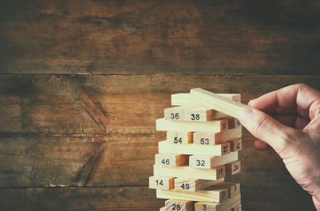 fragile economy: male hand placing wooden block on a tower. planing and strategy concept
