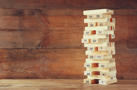 investing risk: wooden tower of wooden blocks with numbers on it. planing and strategy concept