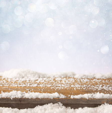 december: image of wooden old table and december fresh snow on top. in front of glitter background
