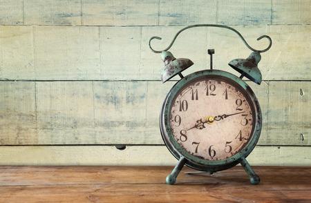 imagen del reloj de alarma de la vendimia en la mesa de madera delante de fondo de madera. retro filtrada