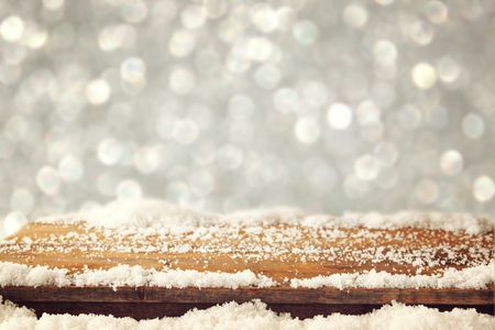 fresh snow: image of wooden old table and december fresh snow on top. in front of glitter background