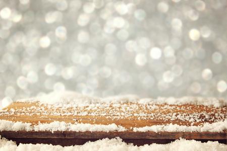 december: imagen de la mesa de madera vieja y diciembre nieve fresca en la parte superior. delante de fondo brillo Foto de archivo