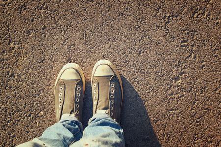 Bild Draufsicht von Person mit Schuhen über Asphaltstraße