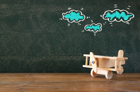 image: image of old wooden airplane toy on wooden table in front of set of infographics over textured chalkboard